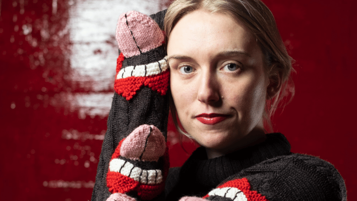 Textile designer Ýr Jóhannsdóttir wearing one of her own creations, a sweater covered in knitted mouths and tongues.