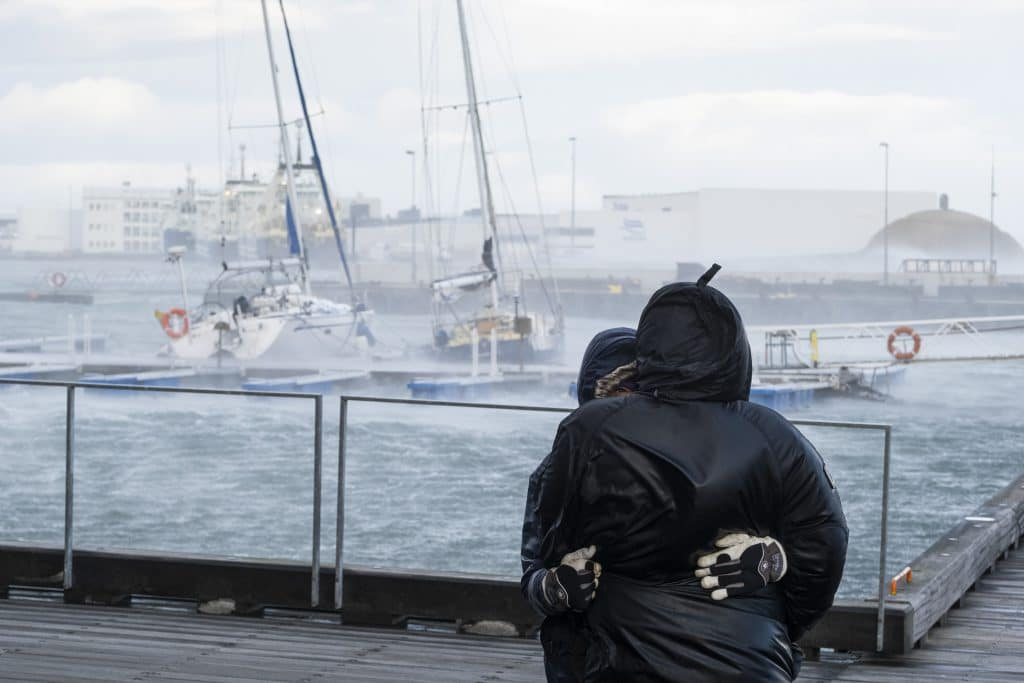 Tourists watch boats in Reykjavík marina during extreme weather